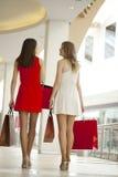 Deux amies sur des achats marchent dans le centre commercial avec des sacs Photographie stock
