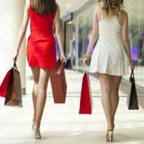Deux amies sur des achats marchent dans le centre commercial avec des sacs Photo stock