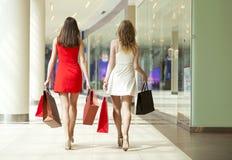 Deux amies sur des achats marchent dans le centre commercial avec des sacs Image libre de droits