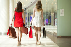 Deux amies sur des achats marchent dans le centre commercial avec des sacs Photos libres de droits