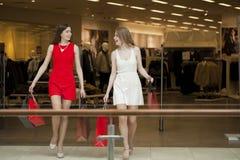 Deux amies sur des achats marchent dans le centre commercial avec des sacs Image stock
