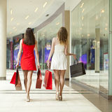 Deux amies sur des achats marchent dans le centre commercial avec des sacs Photographie stock libre de droits