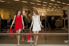 Deux amies sur des achats marchent sur le centre commercial avec des sacs Images stock