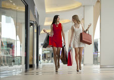 Deux amies sur des achats marchent sur le centre commercial avec des sacs Photos stock