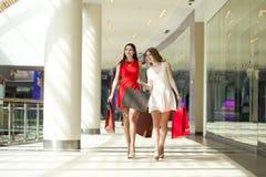 Deux amies sur des achats marchent sur le centre commercial avec des sacs Photo stock