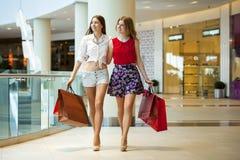 Deux amies sur des achats marchent sur le centre commercial avec des sacs Image libre de droits