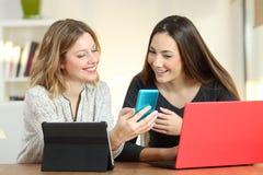 Deux amis à l'aide des dispositifs multiples à la maison image libre de droits