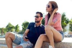Deux amis à l'aide du téléphone portable et écoutant la musique dans le streptocoque Photographie stock