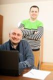 Deux amis à l'ordinateur dans la maison Photo libre de droits