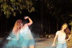 Deux amis émotifs de jeune femme ayant l'amusement avec éclater Holi Photo stock