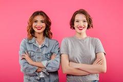 Deux amis émotifs heureux de femmes se tenant d'isolement Photographie stock