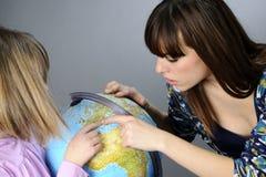Deux amis étudiant sur le globe Photo stock