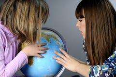 Deux amis étudiant sur le globe Images stock