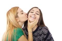 Deux amis adolescents affectueux drôles riant et embrassant Images stock