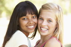 Deux amis adolescents féminins détendant en parc ensemble Image libre de droits