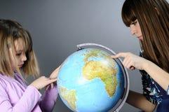 Deux amis affichant sur le globe Images stock