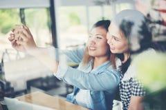 Deux amis appréciant étendant le selfie ainsi que le reflecti de fenêtre Photographie stock libre de droits