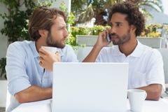 Deux amis appréciant le café ainsi que l'ordinateur portable Image stock