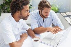 Deux amis appréciant le café ainsi que l'ordinateur portable Photographie stock libre de droits