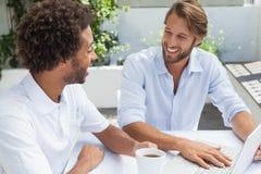 Deux amis appréciant le café ainsi que l'ordinateur portable Images stock