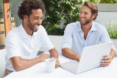 Deux amis appréciant le café ainsi que l'ordinateur portable Photo stock