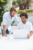 Deux amis appréciant le café ainsi que l'ordinateur portable Photographie stock
