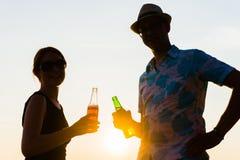 Deux amis appréciant un coucher du soleil sur une plage et buvant de la bière Images stock