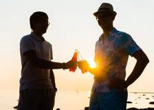 Deux amis appréciant un coucher du soleil sur une plage et buvant de la bière Image libre de droits
