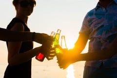 Deux amis appréciant un coucher du soleil sur une plage et buvant de la bière Photographie stock libre de droits