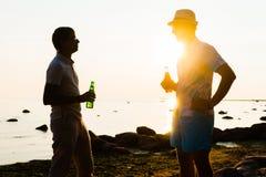 Deux amis appréciant un coucher du soleil sur une plage et buvant de la bière Images libres de droits