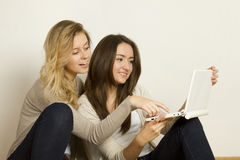 Deux amis attirants à la maison avec l'ordinateur portatif Images stock