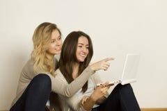 Deux amis attirants à la maison avec l'ordinateur portatif Photo libre de droits