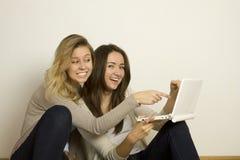 Deux amis attirants à la maison avec l'ordinateur portatif Photographie stock libre de droits