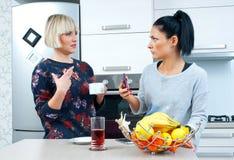 Deux amis attirants de femme buvant le café et parler Photographie stock
