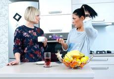 Deux amis attirants de femme buvant le café et parler Image libre de droits