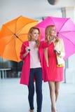 Deux amis attirants marchant avec des parapluies Image stock