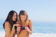 Deux amis attirants regardant les photos qu'elles ont juste prises Image stock