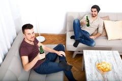 Deux amis avec de la bière et puces dans le salon photographie stock libre de droits