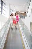 Deux amis avec des achats sur l'escalator Image libre de droits