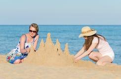 Deux amis avec le château de sable Photographie stock