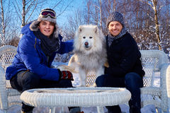 Deux amis avec le chien passent des vacances d'hiver ensemble au cottage de montagne Images stock