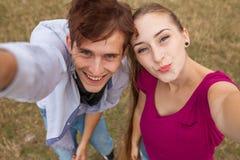 Deux amis avec le téléphone portable prenant des selfies Jeunes adultes Image stock