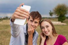 Deux amis avec le téléphone portable prenant des selfies Jeunes adultes Photographie stock libre de droits