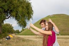 Deux amis avec le téléphone portable prenant des selfies Jeunes adultes Image libre de droits