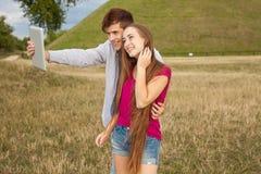 Deux amis avec le téléphone portable prenant des selfies Jeunes adultes Photos stock