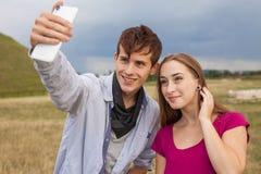 Deux amis avec le téléphone portable prenant des selfies Jeunes adultes Images libres de droits