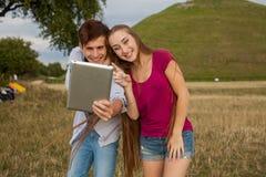 Deux amis avec le téléphone portable prenant des selfies Jeunes adultes Images stock