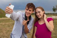 Deux amis avec le téléphone portable prenant des selfies Jeunes adultes Photos libres de droits