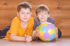 Deux amis avec une boule se trouvant sur le plancher Images stock