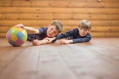 Deux amis avec une boule se trouvant sur le plancher Photos libres de droits